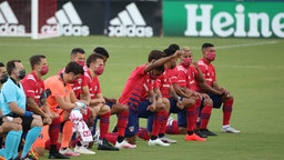 FRISCO, TX - AUGUST 12: FC Dallas Team get to their knees during the national anthem prior the game game between FC Dallas and Nashville SC as part of the Major League Soccer 2020 at Toyota Stadium on August 12, 2020 in Frisco, Texas. (Photo by Omar Vega/Getty Images)
