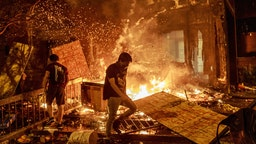 Protesters walk past burning debris outside the Third Police Precinct on May 28, 2020 in Minneapolis, Minnesota, during a protest over the death of George Floyd, an unarmed black man, who died after a police officer kneeled on his neck for several minutes.