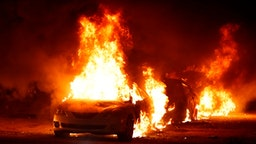 Flames roar from cars torched by protestors a few blocks from the County Court House during a demonstration against the shooting of Jacob Blake, who was shot in the back multiple times by police the day before, prompting community protests in Kenosha, Wisconsin on August 24, 2020. - Police fired tear gas on August 24 when a protest demanding racial justice in the city of Kenosha in Wisconsin turned violent, as rage builds once more in the US at the shooting of a black man by a white officer.