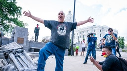 SAINT PAUL, MN,- JUNE 10: Mike Forcia, of the Black River Anishinabe, celebrated after the Christopher Columbus statue was toppled in front of the Minnesota State Capitol in St. Paul on Wednesday, June 10, 2020.