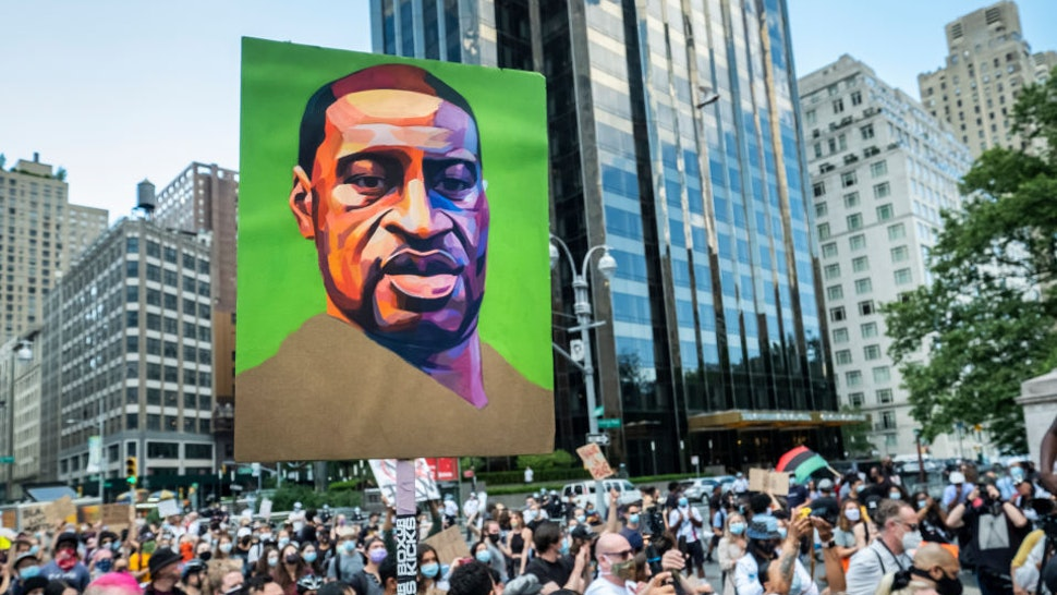"""Hundreds of people pack into Columbus Circle to hear speeches against police violence while one of them holds a painted portrait of George Floyd in front of Trump International Hotel and Tower at Columbus Circle. This was part of the Warriors of the Garden Peaceful Protest Against the 45 President Of the United States Donald J.Trump on his 74th Birthday which0 started at Trump International Tower and drew large crowds. Protesters continue taking to the streets across America and around the world after the killing of George Floyd at the hands of a white police officer Derek Chauvin that was kneeling on his neck during for eight minutes, was caught on video and went viral. During his arrest as Floyd pleaded, """"I Can't Breathe"""". The protest are attempting to give a voice to the need for human rights for African American's and to stop police brutality against people of color. They are also protesting deep-seated racism in America. Many people were wearing masks and observing social distancing due to the coronavirus pandemic. Photographed in the Manhattan Borough of New York on June 14, 2020, USA. (Photo by Ira L. Black/Corbis via Getty Images)"""
