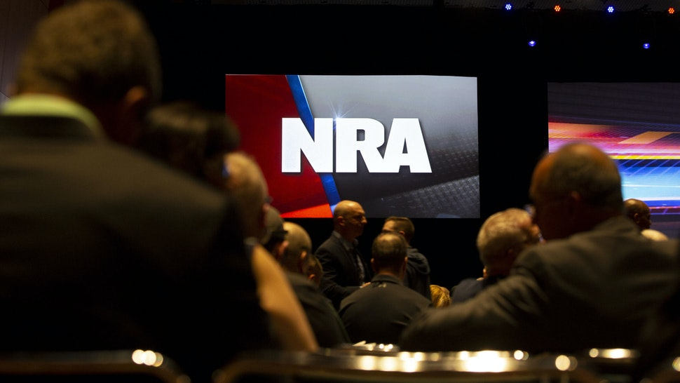 An National Rifle Association (NRA) logo is displayed above members during the NRA annual meeting of members in Indianapolis, Indiana, U.S., on Saturday, April 27, 2019. Retired U.S. Marine Corps Lieutenant Colonel Oliver North has announced that he will not serve a second term as the president of the NRA amid inner turmoil in the gun-rights group. Photographer: Daniel Acker/Bloomberg via Getty Images