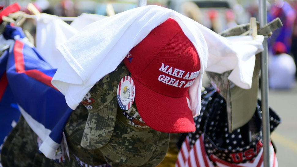 A red Make America Great Again hat sits atop of a rack with camouflage and patriotic hats as supporters wait in line hours ahead of a Trump campaign rally at the Williamsport Regional Airport, in Montoursville, PA on May 20, 2019. (Photo by Bastiaan Slabbers/NurPhoto via Getty Images)