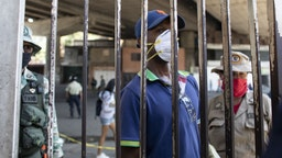 A person wearing a protective mask waits behind a security gate outside of the Ana Francisca Perez de Leon Hospital in the Petare neighborhood of Caracas, Venezuela, on Wednesday, April 15, 2020.