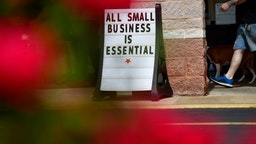 "A man walks his dog past a placard stating ""ALL SMALL BUSINESS IS ESSENTIAL"" outside Atilis Gym on May 20, 2020 in Bellmawr, New Jersey."