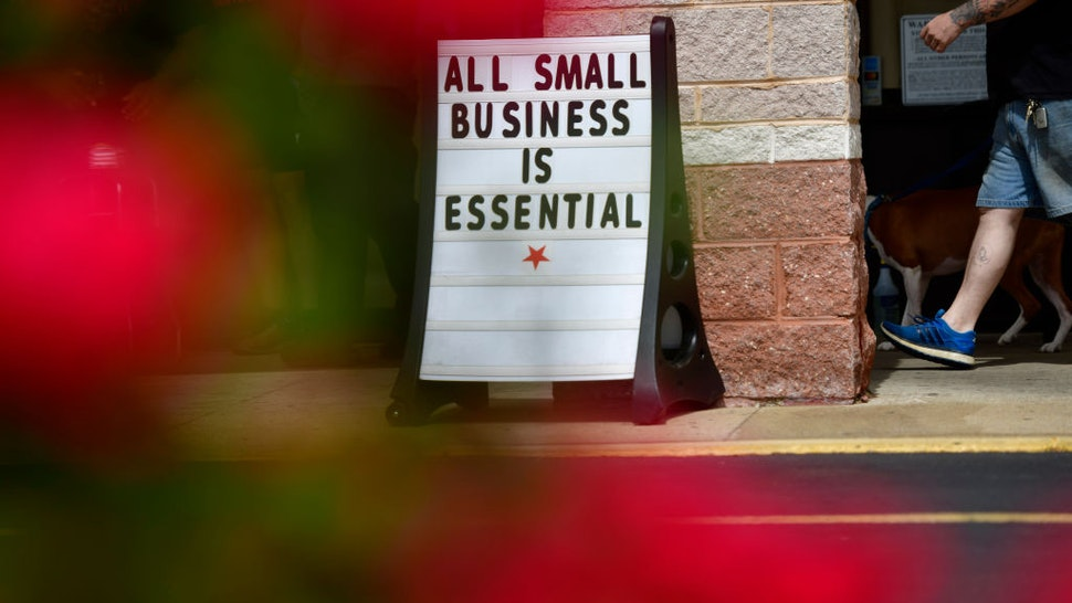 """A man walks his dog past a placard stating """"ALL SMALL BUSINESS IS ESSENTIAL"""" outside Atilis Gym on May 20, 2020 in Bellmawr, New Jersey."""