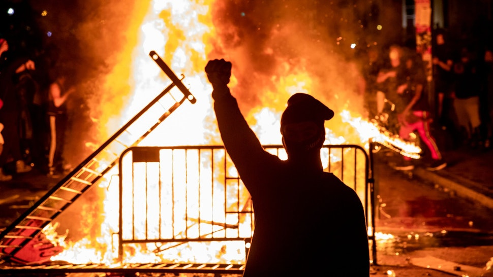TOPSHOT - A protester raises a fist near a fire during a demonstration outside the White House over the death of George Floyd at the hands of Minneapolis Police in Washington, DC, on May 31, 2020. - Thousands of National Guard troops patrolled major US cities after five consecutive nights of protests over racism and police brutality that boiled over into arson and looting, sending shock waves through the country. The death Monday of an unarmed black man, George Floyd, at the hands of police in Minneapolis ignited this latest wave of outrage in the US over law enforcement's repeated use of lethal force against African Americans -- this one like others before captured on cellphone video. (Photo by Samuel Corum / AFP) (Photo by SAMUEL CORUM/AFP via Getty Images)