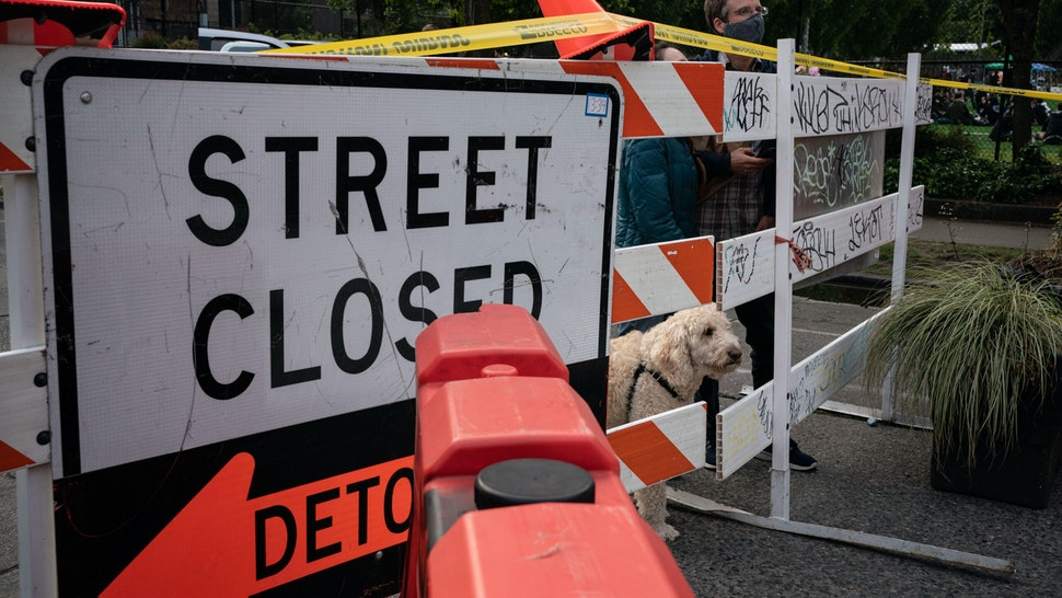 """SEATTLE, WA - JUNE 10: People peer through a barrier with their dog at an entrance to the so-called """"Capitol Hill Autonomous Zone"""" on June 10, 2020 in Seattle, Washington. The zone includes the blocks surrounding the Seattle Police Departments East Precinct, which was the site of violent clashes with Black Lives Matter protesters, who have continued to demonstrate in the wake of George Floyds death. (Photo by David Ryder/Getty Images)"""
