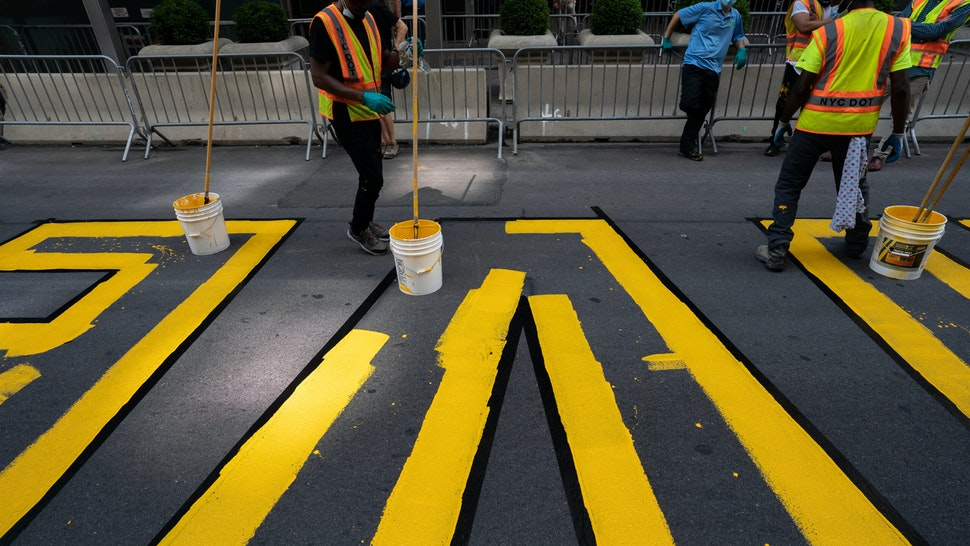 """NEW YORK, NY - JULY 09: Crews begin painting a Black Lives Matter mural on Fifth Avenue directly in front of Trump Tower on July 9, 2020 in New York City. In a tweet, President Trump called the mural a """"symbol of hate"""" and said that it would be """"denigrating this luxury Avenue"""". (Photo by David Dee Delgado/Getty Images)"""