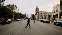 Pedestrians cross a street in the East Market District (also referred to as NuLu neighborhood) in Louisville, Kentucky, U.S., on Thursday, July 23, 2020.