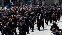 "Graphic content / Members of the ""Not Fucking Around Coalition"" (NFAC), an all black militia, march during a rally to protest the killing of Breonna Taylor, in Louisville, Kentucky on July 25, 2020."