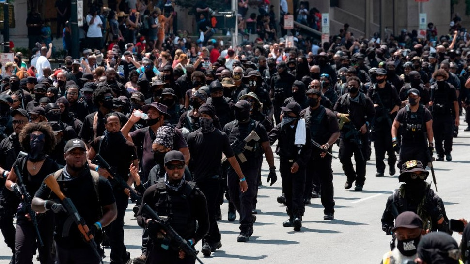 """Graphic content / Members of the """"Not Fucking Around Coalition"""" (NFAC), an all black militia, march during a rally to protest the killing of Breonna Taylor, in Louisville, Kentucky on July 25, 2020."""