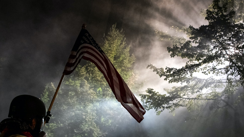 A demonstrators holding a US flag stands in a cloud of tear gas outside the Mark O. Hatfield Federal Courthouse during a night of protest against racial injustice, police brutality and the deployment of federal troops to US cities on July 29, 2020 in Portland, Oregon. - Protests in the US city of Portland have continued for more than 60 days. President Donald Trump's administration on July 29 agreed to a deal to defuse weeks of clashes with the withdrawal of federal forces whose presence enraged protesters, but the timing remained in dispute. (Photo by Alisha JUCEVIC / AFP) (Photo by ALISHA JUCEVIC/AFP via Getty Images)