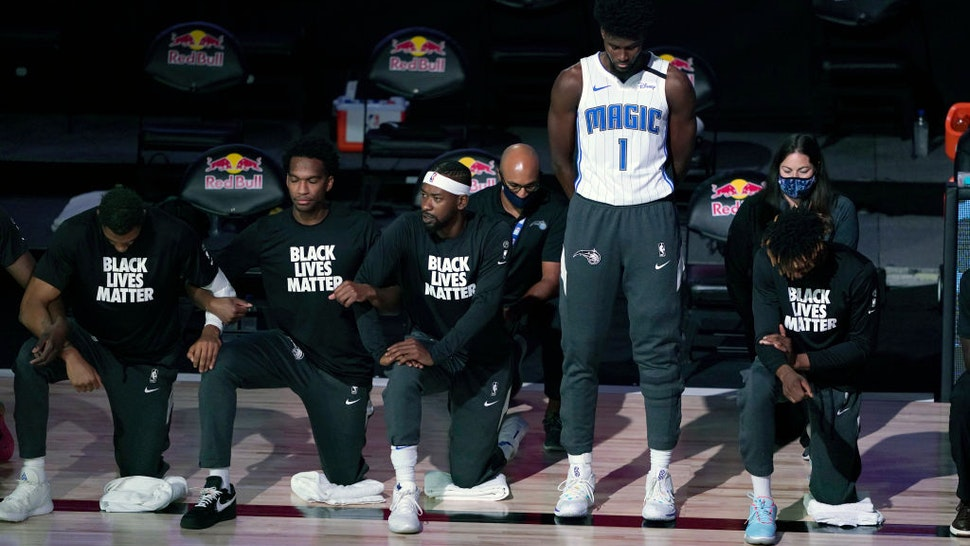 Jonathan Isaac #1 of the Orlando Magic stands as others kneel before the start of a game between the Brooklyn Nets and the Orlando Magic on July 31, 2020