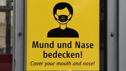 """02 August 2020, Bavaria, Munich: A sign with the inscription """"Cover your mouth and nose"""" can be seen on an elevator at the Theresienstraße subway station. Photo: Felix Hörhager/dpa (Photo by Felix Hörhager/picture alliance via Getty Images)"""