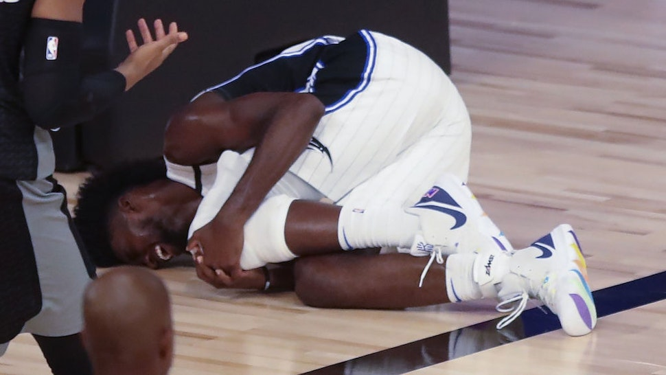 Orlando Magic forward Jonathan Isaac lays on the court holding his left knee after falling during a play in the fourth quarter against the Sacramento Kings on Sunday, Aug. 2, 2020 at Disney's Wide World of Sports' HP Field House in Lake Buena Vista, Florida.