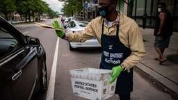 Demario Thurmond, 23, staff with the Detroit Department of Elections collects absentee ballots from a voter during Michigan Primary in Detroit, Michigan on Tuesday, August 4, 2020.
