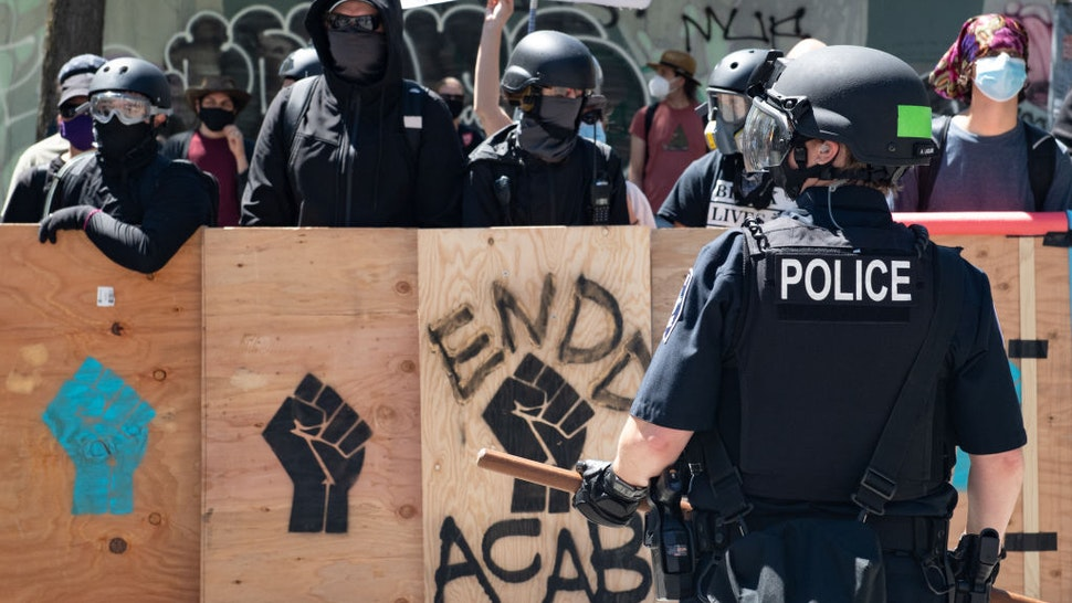 A police officer stands in front of counter protesters during the Seattle Police Officers Guildâs rally to stop defunding of the Seattle Police Department on Sunday, August 9, 2020 at Seattle City Hall.