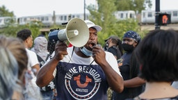 A man shouts into a megaphone against the presence of protesters during a rally against Chicago Police violence in the Englewood neighborhood of Chicago, Illinois, on August 11, 2020. (Photo by KAMIL KRZACZYNSKI / AFP) (Photo by KAMIL KRZACZYNSKI/AFP via Getty Images)