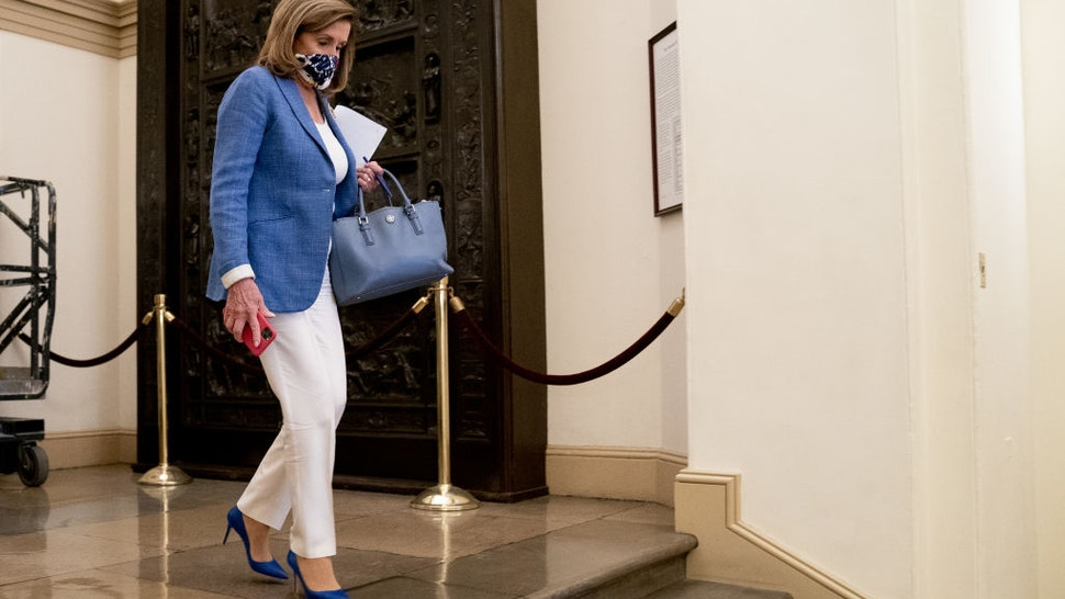 U.S. House Speaker Nancy Pelosi, a Democrat from California, departs her office in the U.S. Capitol in Washington, D.C., U.S., on Friday, Aug. 14, 2020. There's little chance of agreement on a new federal coronavirus relief plan without a compromise on the roughly $1 trillion in aid to beleaguered state and local government that Democrats demand and the White House opposes. Photographer: Erin Scott/Bloomberg via Getty Images