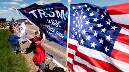 Supporters wave flags outside of Mankato Regional Airport as President Donald Trump makes a campaign stop on August 17, 2020 in Mankato, Minnesota.