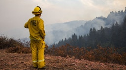 Dustin Blumenthal of the Graton Fire Department watches over spot fires on Big Ridge, seen smoldering in the background, during the Walbridge portion of the LNU Lightning Complex fire in Sonoma County, California, U.S., on Saturday, Aug. 22, 2020. More than 360 blazes are burning in California, forcing mass evacuations in the northern part of the state and creating an air quality emergency. Photographer: Philip Pacheco/Bloomberg via Getty Images