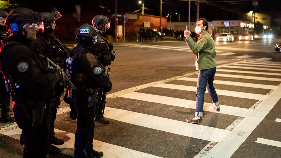 A protester makes a hand gesture toward Portland police officers after they dispersed a crowd from in front of the Portland Police Association (PPA) building early in the morning on August 29, 2020 in Portland, Oregon.