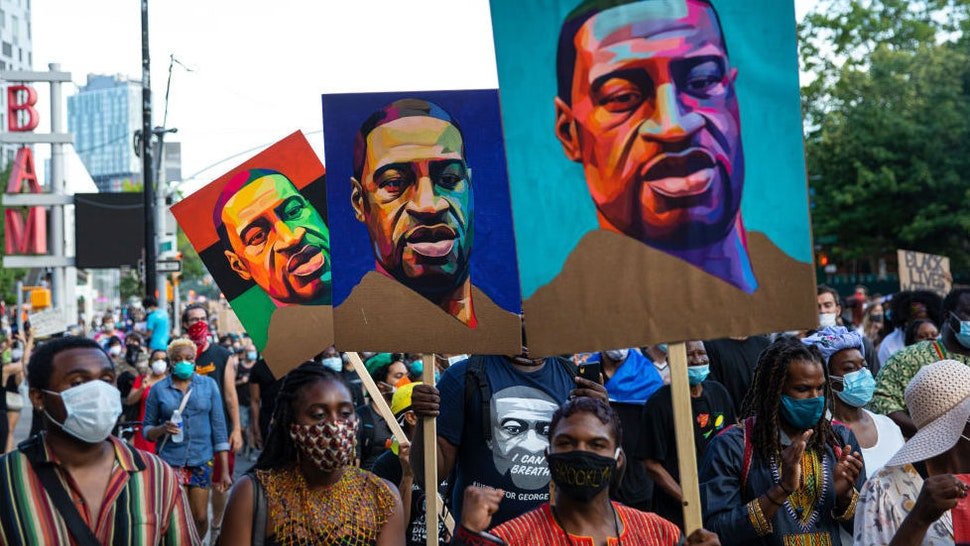 Pedestrians carry posters with the picture of George Floyd who was killed in police custody three weeks earlier in Minneapolis, Minnesota during the Juneteenth protest march on June 19, 2020 in the Brooklyn borough of New York City.