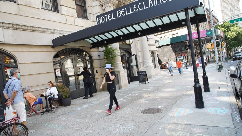 """""""All are welcome"""" is written in chalk on the pavement at Hotel Belleclaire on the Upper West Side of Manhattan"""