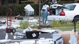 People load merchandise into a car near a looted Best Buy store after parts of the city had widespread looting and vandalism, on August 10, 2020 in Chicago, Illinois.