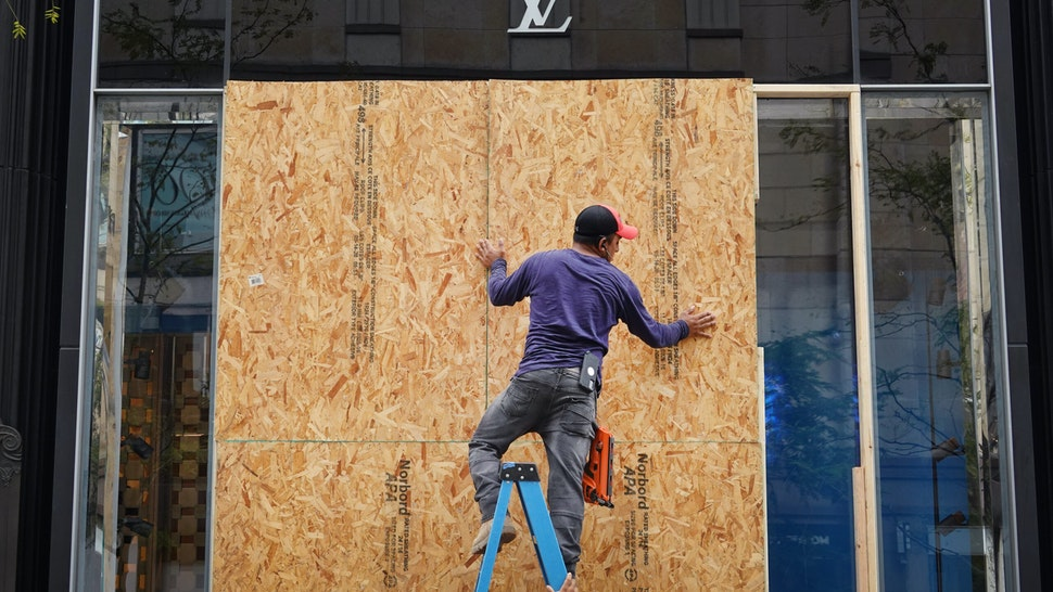CHICAGO, ILLINOIS - AUGUST 10: Workers make repairs to the Louis Vuitton store after it was looted on August 10, 2020 in Chicago, Illinois. Police made more than 100 arrests during the night as widespread looting and disorderly conduct was reported downtown and other areas of the city. Officials believe the violence had apparently grown out of a shoot out between police and a suspect. (Photo by Scott Olson/Getty Images)