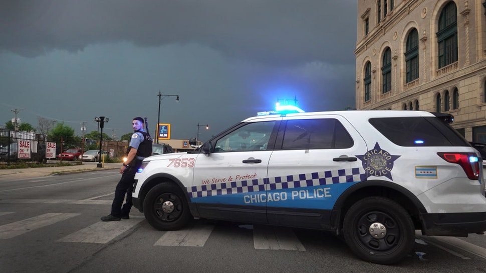 CHICAGO, ILLINOIS - AUGUST 10: A police officer stands guard following unrest on the city's westside moments before a derecho storm hits the area on August 10, 2020 in Chicago, Illinois. The storm, with winds gusts close to 100 miles per hour, downed trees and power lines as it moved through the city and suburbs. (Photo by Scott Olson/Getty Images)