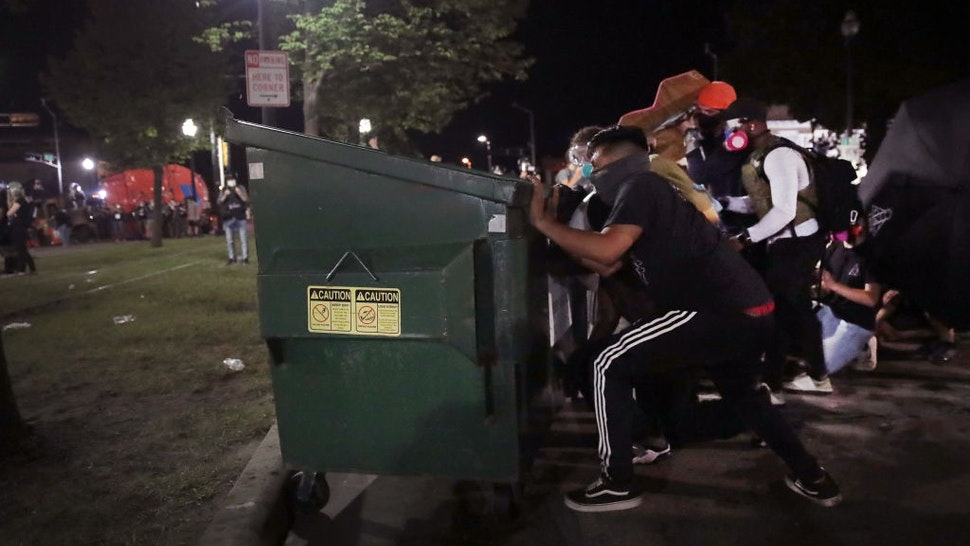 Protesters take cover behind a dumpster as they confront police in front of the Kenosha County Courthouse during a third night of unrest on August 25, 2020 in Kenosha, Wisconsin.
