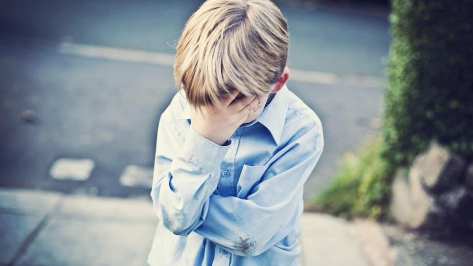 Sad boy with his head in hand - stock photo