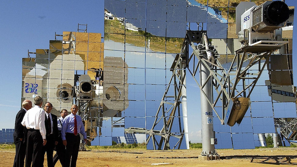 US President George W. Bush (R) walk past a parabolic dish during a tour of the Department of Energy's National Solar Thermal Test Facility at Sandia National Laboratories