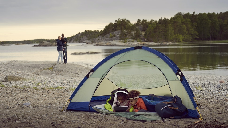 Siblings lying with digital tablet in tent while parents standing at beach during sunset
