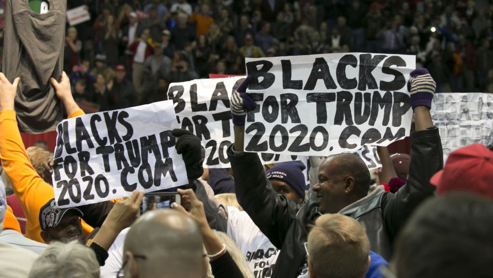 "Attendees hold ""Blacks For Trump"" during a campaign rally with U.S. President Donald Trump in Pensacola, Florida, U.S., on Friday, Dec. 8, 2017."