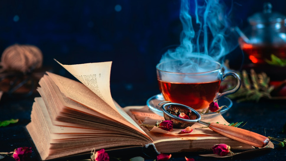 Steaming cup of tea on an open book with curly pages. Herbal drink with rose petals. Dark food photography with copy space. - stock photo