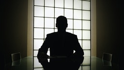 Business man or boss in silhouette interview - stock photo