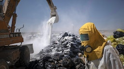 An Iranian worker wearing a protective suit as a loader covers infectious wastes with lime in Tehran Garbage Disposal Center, following the new coronavirus disease (COVID-19) outbreak in Iran, June 7, 2020.