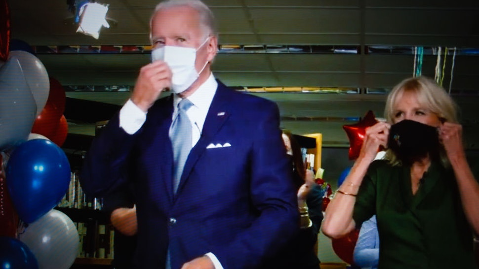 Former US Vice President Joe Biden, with wife Jill Biden, puts on a mask after formally becoming Democratic nominee for president during the virtual 2020 Democratic National Convention, livestreamed online and viewed on a laptop screen from London, England, on August 19, 2020. The four-day event, initially postponed from July, is taking place almost wholly remotely in response to the coronavirus pandemic. Biden will face President Donald Trump in the US presidential election on November 3. (Photo by David Cliff/NurPhoto via Getty Images)