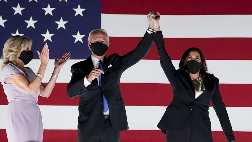 Former Vice President Joe Biden, Democratic presidential nominee, second left, and Senator Kamala Harris, Democratic vice presidential nominee, wear protective masks while holding hands next to Jill Biden, left, outside the Chase Center during the Democratic National Convention in Wilmington, Delaware, U.S., on Thursday, Aug. 20, 2020. Biden accepted the Democratic nomination to challenge President Donald Trump, urging Americans in a prime-time address to vote for new national leadership that will overcome deep U.S. political divisions. Photographer: Stefani Reynolds/Bloomberg