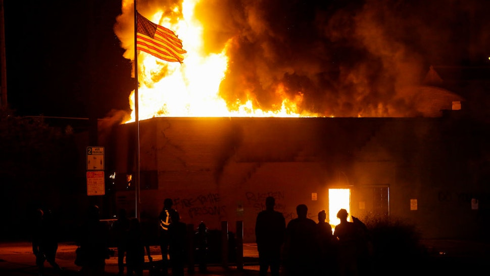 KENOSHA, WI - AUGUST 24: People watch a the American flag flies over a burning building during a riot as demonstrators protest the police shooting of Jacob Blake on Monday, August 24, 2020 in Kenosha, Wisconsin. Blake was shot in the back multiple times by police officers responding to a domestic dispute call yesterday.