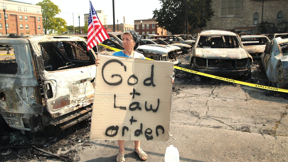 KENOSHA, WISCONSIN - AUGUST 24: A women holds a sign while standing in a used car lot with burned out cars after a night of unrest, on August 24, 2020 in Kenosha, Wisconsin. The unrest stemmed from an incident in which police shot a Black man multiple times in the back as he entered the driver's side door of a vehicle.
