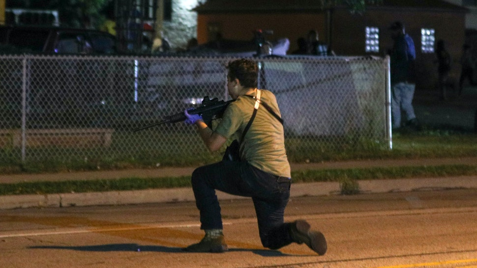 KENOSHA, WISCONSIN, USA - AUGUST 25: (EDITORS NOTE: Image contains graphic content.) A man on the ground was shot in the chest as clashes between protesters and armed civilians who protect the streets of Kenosha against the arson during the third day of protests over the shooting of a black man Jacob Blake by police officer in Wisconsin, United States on August 25, 2020.