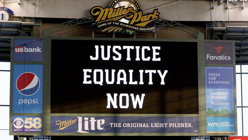 "MILWAUKEE, WISCONSIN - AUGUST 25: The scoreboard displays a message of ""Justice Equality Now"" before the game between the Cincinnati Reds and Milwaukee Brewers at Miller Park on August 25, 2020 in Milwaukee, Wisconsin."