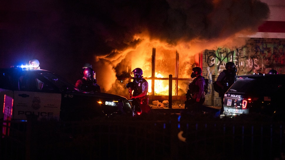 """MINNEAPOLIS, MN - MAY 27: A fire burns inside of an Auto Zone store near the Third Police Precinct on May 27, 2020 in Minneapolis, Minnesota. Businesses near the Third Police Precinct were looted and damaged today as the area has become the site of an ongoing protest after the police killing of George Floyd. Four Minneapolis police officers have been fired after a video taken by a bystander was posted on social media showing Floyd's neck being pinned to the ground by an officer as he repeatedly said, """"I can't breathe"""". Floyd was later pronounced dead while in police custody after being transported to Hennepin County Medical Center."""
