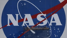 Painters refurbish the NASA logo on the Vehicle Assembly Building at the Kennedy Space Center in Florida in Florida on May 29, 2020. The faded 10-story-tall insignia was last painted 13 years ago. - The SpaceX Falcon 9 rocket with the Crew Dragon capsule is rescheduled to launch to the International Space Station on May 30, carrying astronauts Bob Behnken and Doug Hurley. (Photo by Gregg Newton / AFP) (Photo by GREGG NEWTON/AFP via Getty Images)