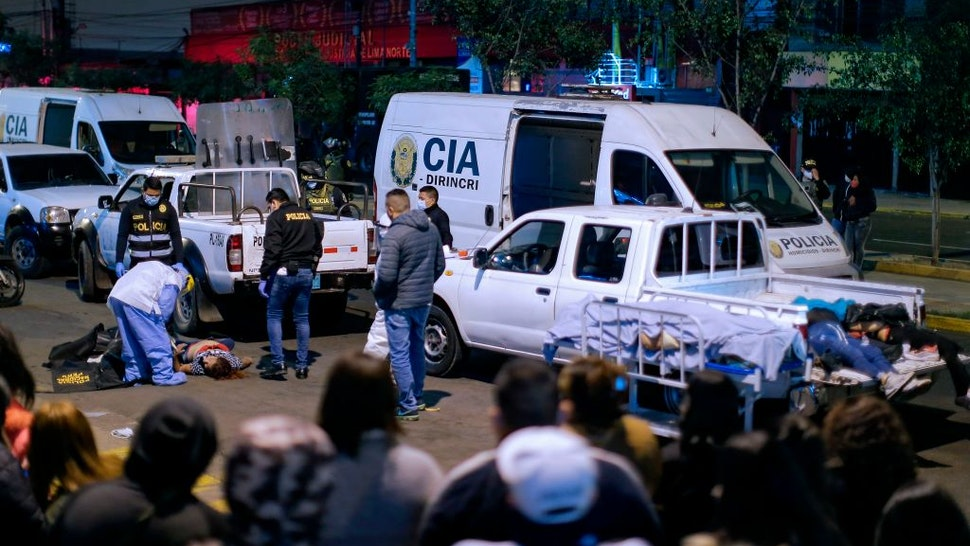 """The bodies of at least 13 people who suffocated in a crush during a raid late on August 22 are being loaded onto pick-up trucks on August 23, 2020 outside the nightclub where a party was being held despite a ban on such gatherings imposed to fight the COVID-19 novel coronavirus pandemic. - At least 13 people suffocated """"when those attending the party tried to escape through the single exit, trampling each other and getting trapped in the stairway,"""" the Peruvian Interior ministry said. This month the country re-imposed a curfew on Sundays in response to the rising number of infections."""