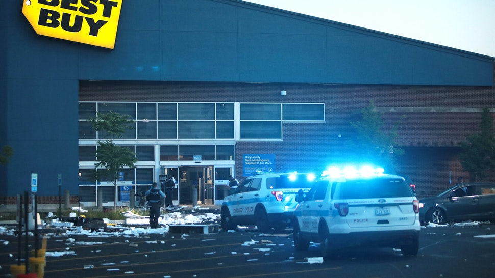 CHICAGO, ILLINOIS - AUGUST 10: A Police officers inspect a damaged Best Buy store after parts of the city had widespread looting and vandalism, on August 10, 2020 in Chicago, Illinois. Police made several arrests during the night of unrest and recovered at least one firearm.